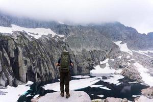 homem com mochila no penhasco de frente para a água e a montanha foto