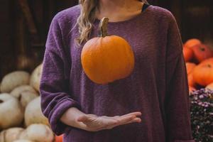 mulher pegando abóbora laranja foto
