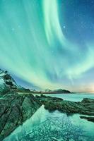montanha rochosa verde e preta ao lado do corpo d'água