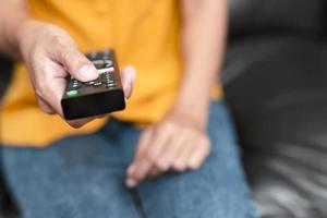 mulher pressionando botões no controle remoto da tv foto