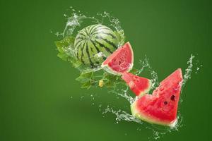 água espirrando na melancia sobre fundo verde foto