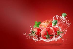 água espirrando em tomates vermelhos frescos foto