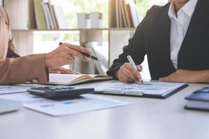conferência de trabalho conjunta, reunião da equipe de negócios presente, colegas investidores discutindo os dados do gráfico financeiro do novo plano na mesa do escritório com laptop e tablet digital, finanças, contabilidade, investimento