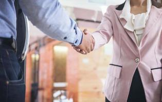 dois colegas de trabalho apertando as mãos foto