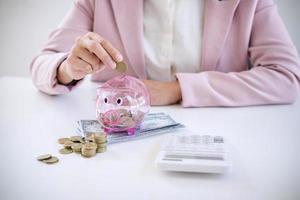 mulher de negócios colocando moedas no cofrinho foto