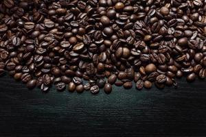 grãos de café sobre um fundo escuro de madeira