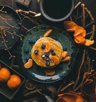 panquecas com rodelas de laranja e mirtilos no prato