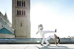 par de artistas de capoeira fazendo um chute foto