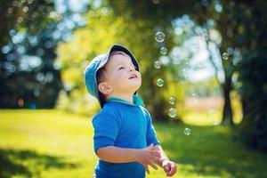criança olhando para bolhas de sabão foto