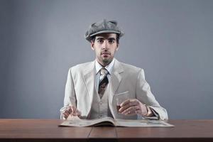 homem da moda da máfia vestindo boné e terno listrado branco. foto