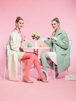duas meninas cabelos loiros anos 50 moda estilo bebendo chá.