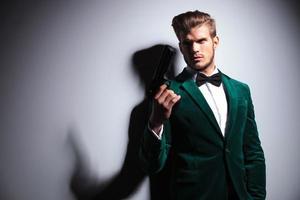 homem em elegante terno de veludo verde segurando uma grande arma
