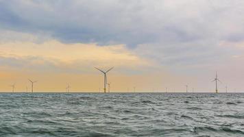 parque eólico offshore ao pôr do sol foto
