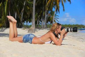 garota na praia do caribe com uma câmera