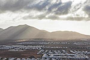 vista sobre a playa blanca à luz da manhã com montanhas