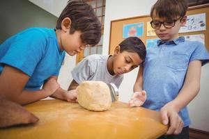alunos olhando para uma pedra com uma lupa