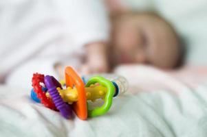 bebê dorme perto de chocalhos foto