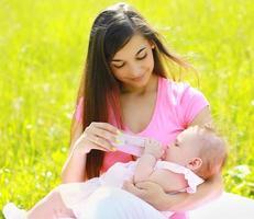 mãe alimentando mamadeira ao ar livre foto