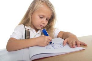 Menina bonita feliz na mesa desenhando no bloco de notas com marcador foto