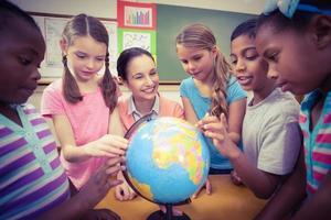 professor e alunos olhando para o globo