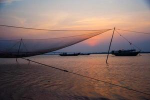 cena calma de rede de pesca contra o pôr do sol roxo. foto