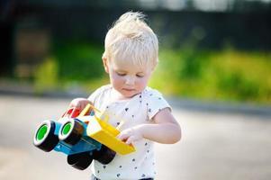 menino brincando com brinquedo de carro foto