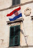 croácia, dubrovnik. a bandeira croata em uma fachada antiga.