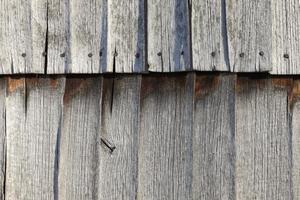 celeiro de madeira desgastado - telhas da fachada ao sol foto