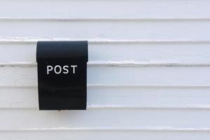caixa de correio preta na parede de madeira branca da casa foto