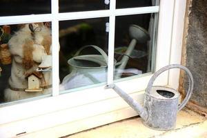 regador no peitoril da janela foto