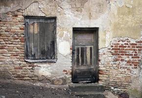 janela velha e porta com parede rachada