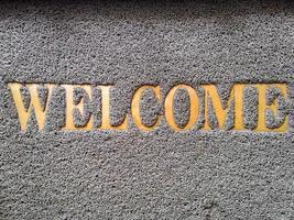 capacho de plástico e palavra de boas-vindas dourada foto