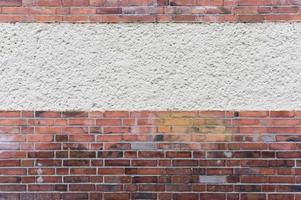 parede externa com área estucada, tijolo vermelho de clínquer, fundo de textura foto