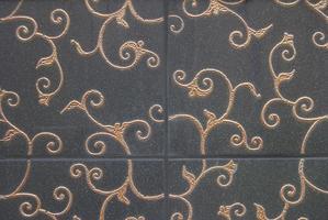 azulejos decorativos escuros com decoração floral dourada foto