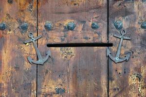 porta de madeira velha com ranhura de correio e âncoras foto