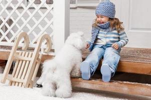 menina com um cachorro na varanda da frente