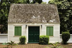 pequena casa com quintal de tijolos e cerca branca foto