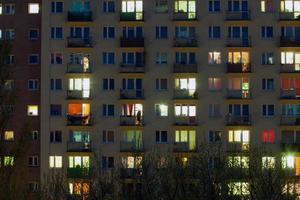 janela de um bloco de apartamentos à noite foto