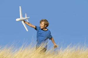 um menino brincando de planador de avião em um campo gramado foto
