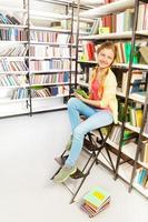 menina com duas tranças e tablet sentada na escada foto