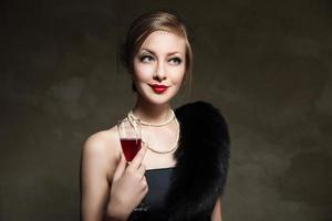 mulher bonita com copo de vinho tinto. Estilo retrô foto