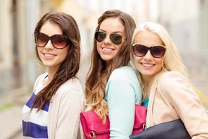 três mulheres sorridentes com óculos escuros e bolsas foto