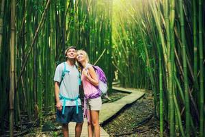 casal caminhando pela floresta de bambu foto