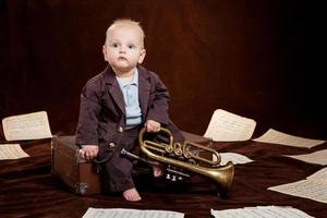 menino caucasiano brincando com trompete entre lençóis com música foto