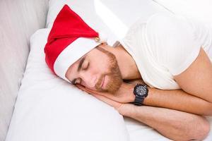 homem com chapéu de Papai Noel dormindo na cama foto