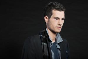 homem bonito moda inverno escuro. tiro do estúdio. usando lenço. foto