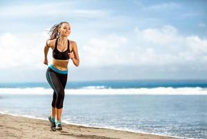 mulher atleta correndo na praia ensolarada foto
