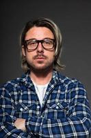 jovem com cabelo loiro e barba, usando óculos retrô.