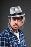 jovem expressivo, com longos cabelos loiros e chapéu ska.