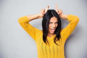 mulher mostrando chifres com os dedos foto